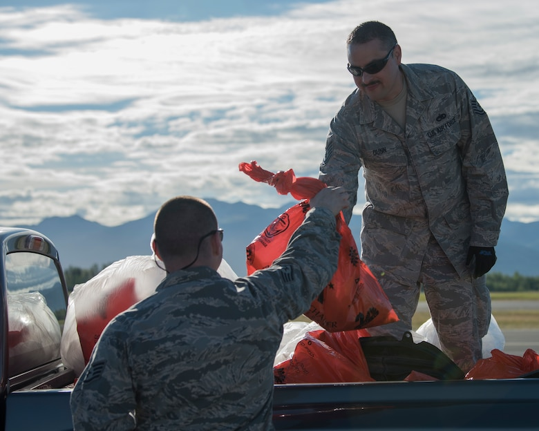 Tech. Sgt. Hayden Dunn, a 3rd Munitions Squadron production flight supervisor receives a bag of trash from Staff Sgt. Kevin Carroll, a 673rd Logistics Readiness Squadron fuels distribution supervisor, after conducting a foreign object and debris walk at Joint Base Elmendorf-Richardson, Alaska, July 2, 2018. The JBER Airmen conducted the FOD walk after the Arctic Thunder Open House to remove debris that could damage aircraft and hinder mission readiness.