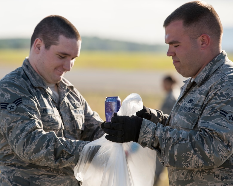 Senior Airman Cody Powers and Airman 1st Class Tyler Parnell, both 3rd Munitions Squadron muntions systems crew chiefs, pick up trash during a foreign object and debris walk at Joint Base Elmendorf-Richardson, Alaska, July 2, 2018. The JBER Airmen conducted the FOD walk after the Arctic Thunder Open House to remove debris that could damage aircraft and hinder mission readiness.