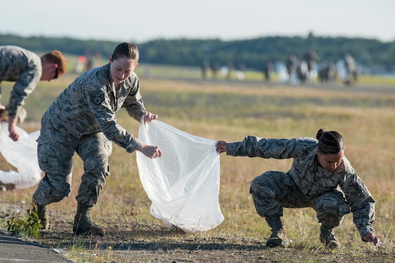 Staff Sgts. Kelsey Padula and Amanda Woodell, both 3rd Munitions Squadron muntions systems crew chiefs, pick up trash during a foreign object and debris walk at Joint Base Elmendorf-Richardson, Alaska, July 2, 2018. The JBER Airmen conducted the FOD walk after the Arctic Thunder Open House to remove debris that could damage aircraft and hinder mission readiness.