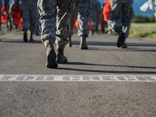 Joint Base Elmendorf-Richardson Airmen walk toward the flight line as they prepare to conduct a foreign object and debris walk at JBER, Alaska, July 2, 2018. The Airmen conducted the FOD walk after the Arctic Thunder Open House to remove debris that could damage aircraft and hinder mission readiness.
