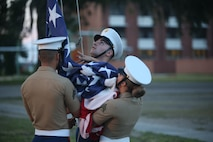 Marines conduct evening colors during an Independence Day celebration aboard Marine Corps Recruit Depot Parris Island July 4. The national ensign is a physical representation of the country. It is a service wide custom to display the colors from sunrise to sunset.