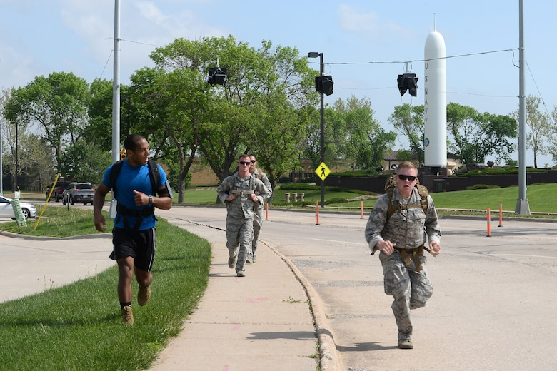 55th Security Forces Squadron Airmen approach the finish line during a ruck march challenge May 14, 2018, at Offutt Air Force, Nebraska. Team two ran and walked 2 miles from the the Patriot Club parking lot to Peacekeeper Drive in 38 minutes and 25 seconds to earn first place in this challenge. (U.S. Air Force photo by Charles J. Haymond)