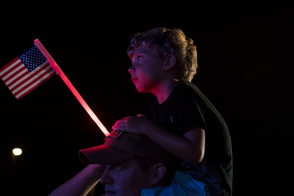 A child watches a live music performance during Patriot Fest, July 3, 2018, at Moody Air Force Base, Ga. Team Moody hosted the free event to allow Airmen and their families an opportunity to take some time away from the mission and enjoy a Fourth of July experience. The event consisted of live music, food trucks, family fun and a fireworks show. (U.S. Air Force photo by Senior Airman Janiqua P. Robinson)