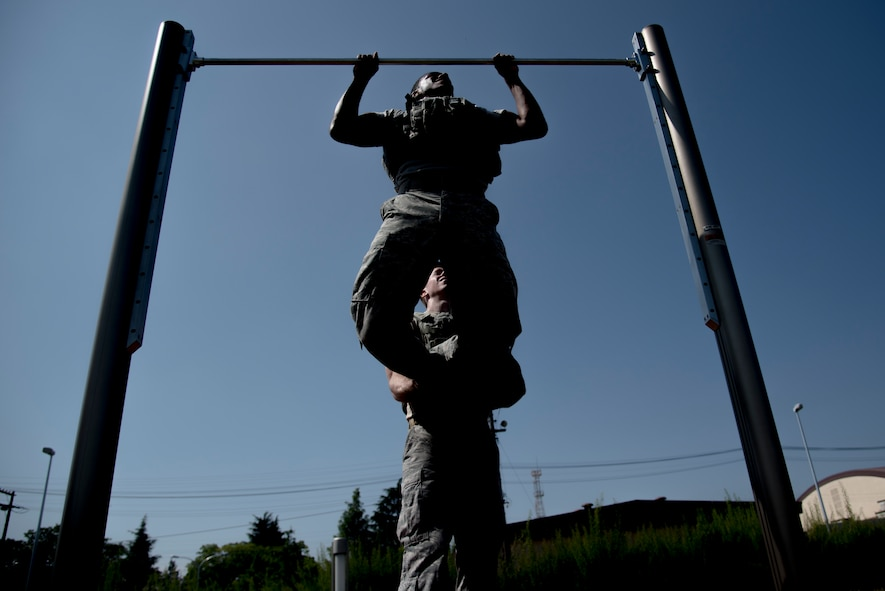 Senior Airman Antonio Gant, 374th Security Forces Squadron 2018 Security Forces Advanced Combat Skills Assessment team member, does pull ups in bullet proof vest during group physical training, June 1, 2018, at Yokota Air Base, Japan.