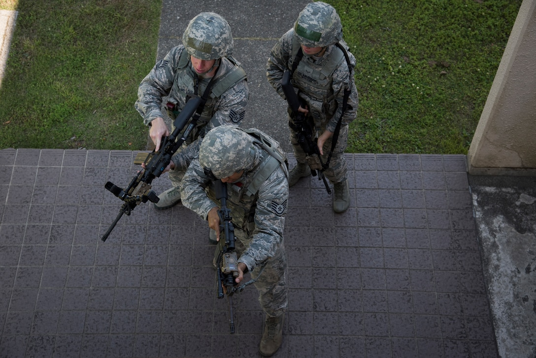 The 374th Security Forces Squadron 2018 Security Forces Advanced Combat Skills Assessment team, enter a building in formation during tactical building clearing training, June 1, 2018, at Yokota Air Base, Japan.