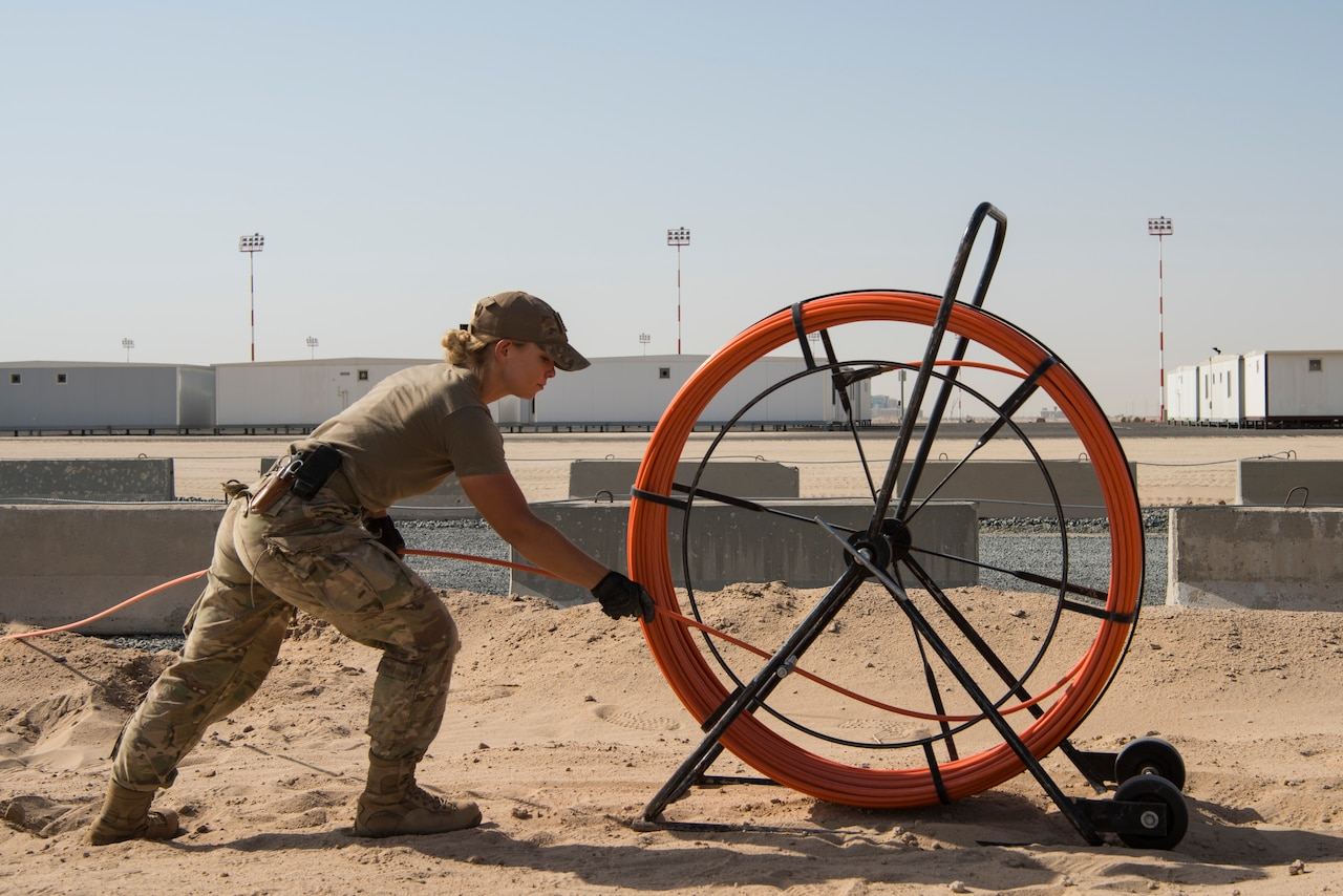 Senior Airman Kelsie Burt, 379th Expeditionary Civil Engineer Squadron cable and antenna systems technician, deployed from Zanesville, Ohio, re-spools communications line at Cargo City, located at Abdullah Al Mubarak Air Base, Kuwait, June 25, 2018. Burt and her team are forward deployed from Al Udeid Air Base, Qatar. (U.S. Air Force photo by Staff Sgt. Joshua King)