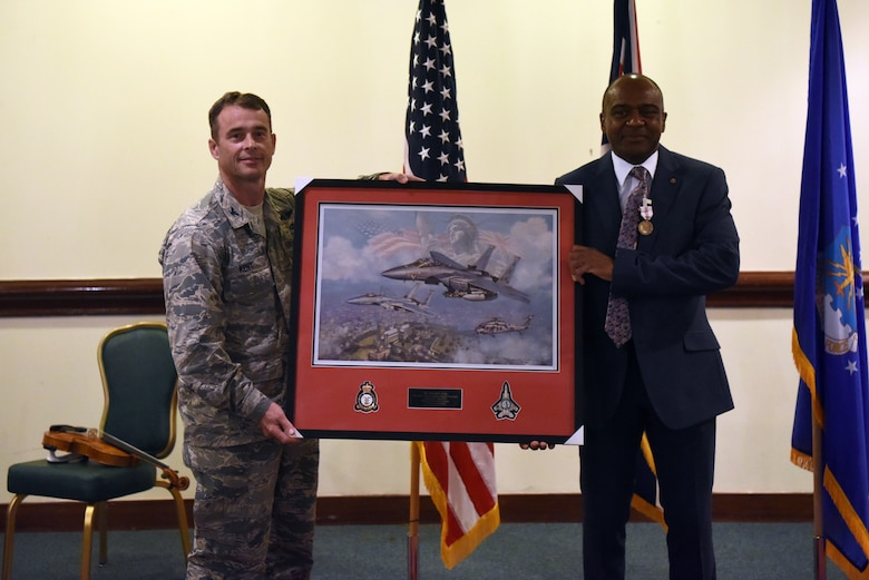 Col. John Kent, 48th Fighter Wing vice commander, presents a farewell gift to Edward Cole, 48th Fighter Wing community support director, during Cole's retirement ceremony at Royal Air Force Lakenheath, England, June 29, 2018. Cole worked at 11 bases during his military career and over six bases during his civil service career. (U.S. Air Force photo/ Airman 1st Class John A. Crawford)