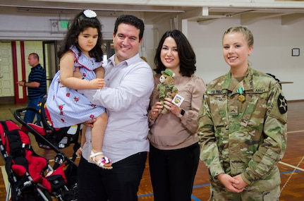 Pvt. Gracie Hilinski, Medical Section, Headquarters and Headquarters Battery, 2nd Battalion, 146th Field Artillery Regiment, 81st Stryker Brigade Combat Team poses with (from left to right) Lilya Soulami, Ayoub Soulami, and Asmae Hram, little girl, and her family, whose life was saved by Hilinski, at a ceremony at the National Guard Armory in Olympia, Wash., June 30, 2018.