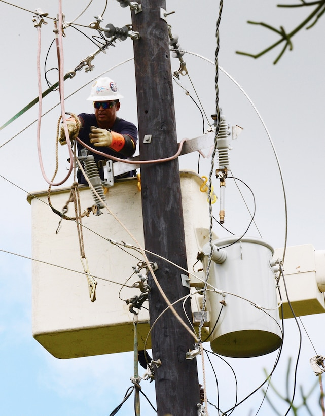 An electrical worker labors on a utility pole, perched high on a bluff, to restore power to 51 clients in Orocovis, Puerto Rico. The workers were contracted by the U.S. Army Corps of Engineers through a mission assignment from the Federal Emergency Management Agency as a result of Hurricane Maria.