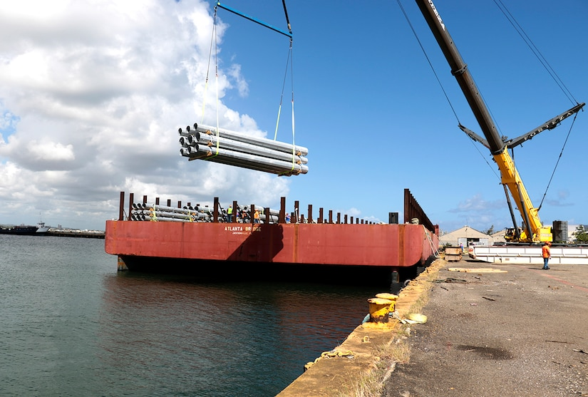 Federal Emergency Management Agency contractors unload utility poles from the barge Atlanta Bridge at Port of San Juan, Puerto Rico.