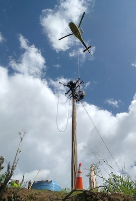 The U.S. Army Corps of Engineers uses helicopters to place poles and electrical power lines in the mountain community of San German, Puerto Rico, in February.
