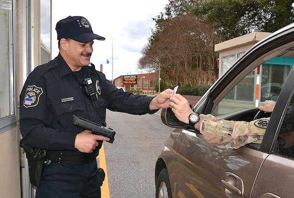 DLA Installation Operations Police Officer Kevin Buhler checks an identification card at the gate of Defense Supply Center Richmond, Virginia, using the Defense Biometric Identification System.