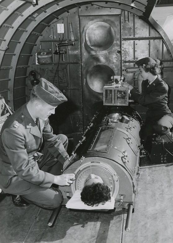 "The ""flying lung"" designed at the U.S. Air Force School of Aviation Medicine in 1952. A flight nurse adjusts and prepares to disconnect the battery used during transport from the hospital to the aircraft, January 29, 1953. Once aboard, the pressure pump plugged directly into the plane's electrical system to power the flying lung during flight. (Photo courtesy of National Archives and Records Administration)"