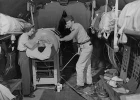 """Airman 3rd Class Warren Beatty in a """"flying lung"""" aboard a 374th Troop Carrier Wing C-54 Skymaster, cared for by 1st Lt. Shirley C. Warren, a flight nurse, and Staff Sgt. Lawrence Kiger, a medical technician, en route from Korea to Japan, July 23, 1953. Beatty, stricken with a lung ailment while stationed at Inchon Harbor, Korea, was the first iron lung patient to receive an airlift from the Korean theater. (Photo courtesy of National Archives and Records Administration)"""
