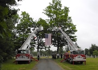 Two fire trucks flew the American flag between two ladders at the Glenwood Cemetery for Army Air Force Staff Sgt. Roy Davis' military burial in Ashby, Massachusetts, June 23, 2018. Along with members of the Ashby Police and Fire departments, members of all five branches of the military attended the funeral to pay their respects to the World War II veteran who paid the ultimate price for freedom.