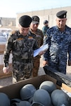 Members of the Iraqi army and police look at ballistic helmets in a container during the divestment of organizational clothing and individual equipment to the Iraqi army and police at the Besmaya Range Complex, Iraq.