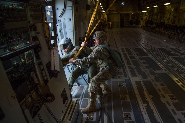 Air Force Master Sgt. Cecil Dickerson, 249th Airlift Squadron loadmaster, left, and an Army jumpmaster with the 4th Infantry Brigade Combat Team (Airborne), 25th Infantry Division, U.S. Army Alaska, recover paratrooper static lines on a C-17 Globemaster III during the Arctic Thunder Open House Special Needs and Department of Defense Family Day at Joint Base Elmendorf-Richardson, Alaska, June 29, 2018. During the biennial open house, the base opens its gates to the public and hosts multiple performers including the U.S. Air Force Thunderbirds, JB Elmendorf-Richardson Joint Forces Demonstration and the U.S. Air Force F-22 Raptor Demonstration Team. (U.S. Air Force photo by Senior Airman Valerie Halbert)