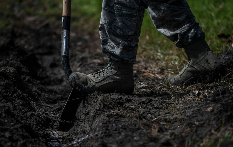 U.S. Air Force Senior Airman Anthony Cooper, a pavements and equipment journeyman with the 1st Special Operations Civil Engineer Squadron, digs a trench to unclog a storm drain during routine maintenance at Hurlburt Field, Fla., June 12, 2018. Air Commandos assigned to the 1st SOCES keep storm drains clear by inspecting, re-excavating and removing or replacing soil and filtered sand to facilitate the draining of sediments to protect the intercoastal waterway. (U.S. Air Force photo by Airman 1st Class Dennis Spain)