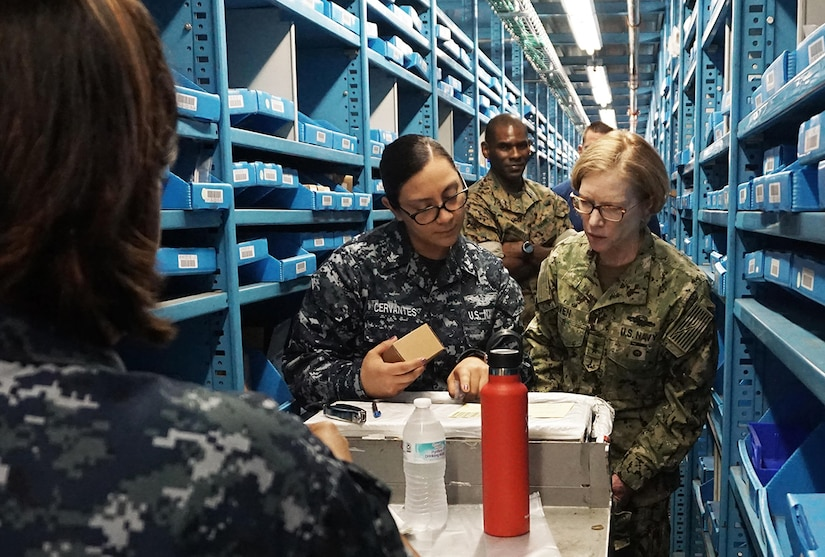Navy Rear Adm. Deborah Haven, director of the DLA Joint Reserve Force, observes the process of picking bin materiel from Navy Petty Officer 2nd Class Elsa Cervantes.