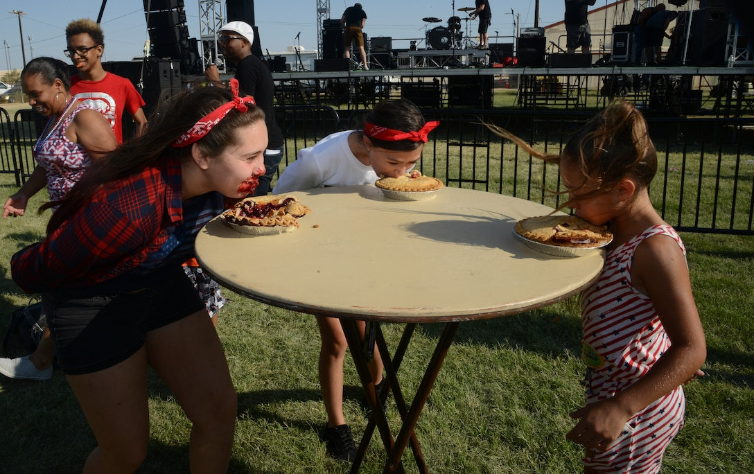 Pie eating contestants eat their way to the end of a pie for a prize at the Summer Bash at Wings Field, July 4. Each pie had a prize such as a gift card at the bottom of the pie tin. (U.S. Air Force photo by Laura Motes)
