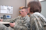 GI Bill Manager Sgt. Eric Rasmussen and Federal Tuition Assistance Manager Sgt. 1st Class Teresa Anthony discuss education benefits in the Minnesota National Guard's Education Office in Saint Paul, Minn.