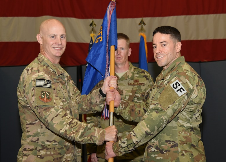 Guidon Transfer Colonel G John Grimm, 90th Security Forces commander, passes the guidon to Col. Nicholas Petren, 90th Security Forces Squadron commander, during the 90th SFS change of command ceremony July 6, 2018 in the Peacekeeper High Bay on F.E. Warren Air Force Base, Wyo. The ceremony signified the transition of command from Lt. Col. Richard Zeigler to Petren. (U.S. Air Force photo by Glenn S. Robertson)