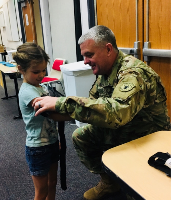 Major Michael Hay, officer-in-charge of the 6th Medical Recruiting Battalion's Phoenix Medical Recruiting Station demonstrates why a tourniquet is not appropriate for small children using Harper Magoteaux's arm. Hay and other medical professionals provided free public training at Maricopa Integrated Health System's Auditorium as part of National Stop the Bleed Day on March 31.