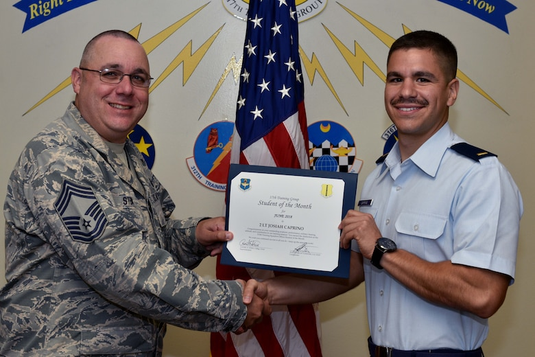 U.S. Air Force Chief Master Sgt. Daniel Stein, 17th Training Group superintendent, presents the 315th Training Squadron Officer Student of the Month award to 2nd Lt. Josiah Caprino, 315th TRS trainee, at Brandenburg Hall on Goodfellow Air Force Base, Texas, July 6, 2018. The 315th TRS's vision is to develop combat-ready intelligence, surveillance and reconnaissance professionals and promote an innovative squadron culture and identity unmatched across the U.S. Air Force. (U.S. Air Force photo by Senior Airman Randall Moose/Released)