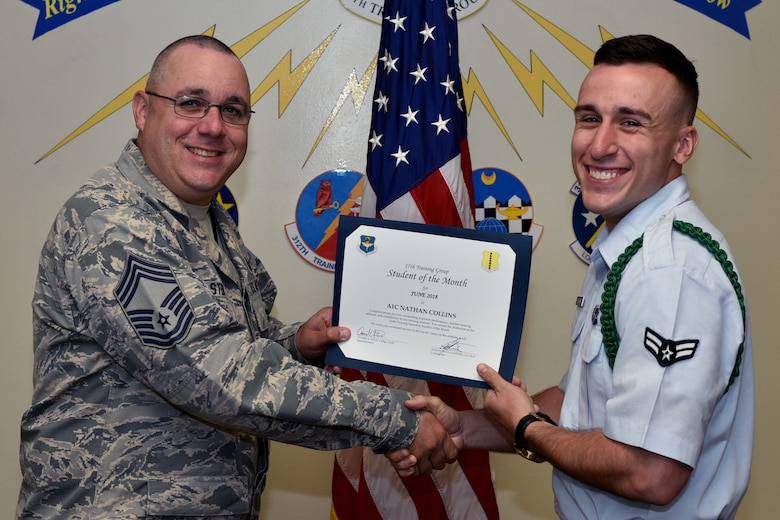 U.S. Air Force Chief Master Sgt. Daniel Stein, 17th Training Group superintendent, presents the 316th Training Squadron Student of the Month award to Airman 1st Class Nathan Collin, 316th TRS trainee, at Brandenburg Hall on Goodfellow Air Force Base, Texas, July 6, 2018. The 316th TRS's mission is to conduct U.S. Air Force, U.S. Army, U.S. Marine Corps, U.S. Navy and U.S. Coast Guard cryptologic, human intelligence and military training. (U.S. Air Force photo by Senior Airman Randall Moose/Released)