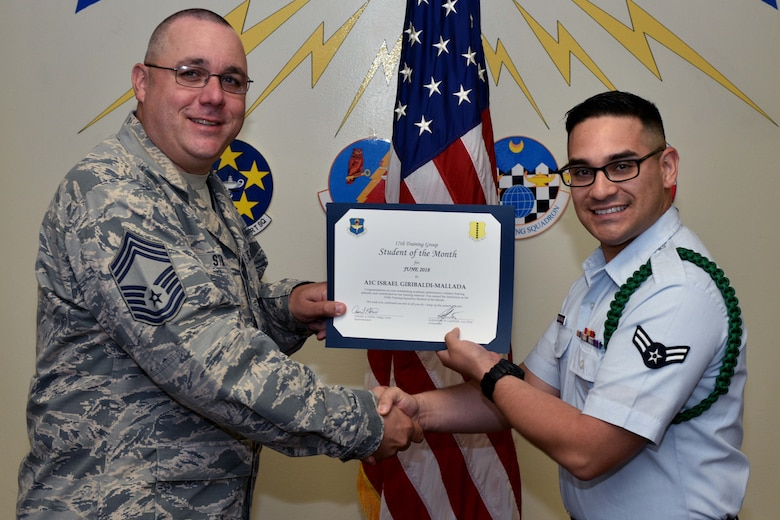 U.S. Air Force Chief Master Sgt. Daniel Stein, 17th Training Group superintendent, presents the 315th Training Squadron Student of the Month award to Airman 1st Class Israel Giribaldi-Mallada, 316th TRS trainee, at Brandenburg Hall on Goodfellow Air Force Base, Texas, July 6, 2018. The 315th TRS's vision is to develop combat-ready intelligence, surveillance and reconnaissance professionals and promote an innovative squadron culture and identity unmatched across the U.S. Air Force. (U.S. Air Force photo by Senior Airman Randall Moose/Released)