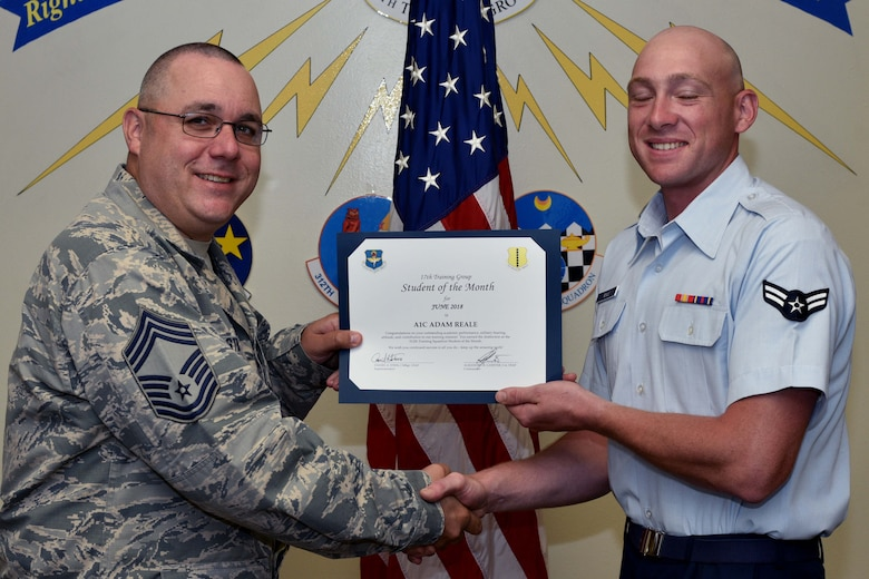 U.S. Air Force Chief Master Sgt. Daniel Stein, 17th Training Group superintendent, presents the 312th Training Squadron Student of the Month award to Airman 1st Class Adam Reale, 312th TRS trainee, at Brandenburg Hall on Goodfellow Air Force Base, Texas, July 6, 2018. The 312th TRS's mission is to provide Department of Defense and international customers with mission ready fire protection and special instruments graduates and provide mission support for the Air Force Technical Applications Center. (U.S. Air Force photo by Senior Airman Randall Moose/Released)