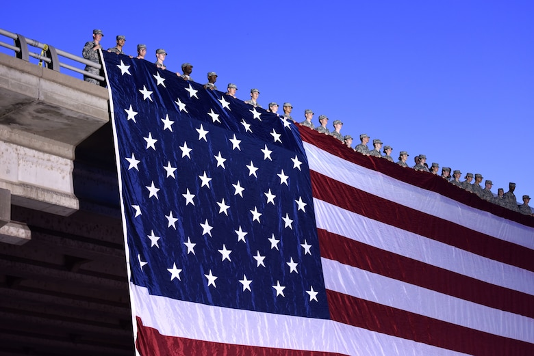 Volunteers from Goodfellow Air Force Base, Texas drape the United States flag over Chadbourne Street bridge during the 31st Annual San Angelo Symphony Pops Concert July 3, 2018. The free concert was held as an early celebration of Independence Day. (U.S. Air Force photo by Airman 1st Class Seraiah Hines/Released)