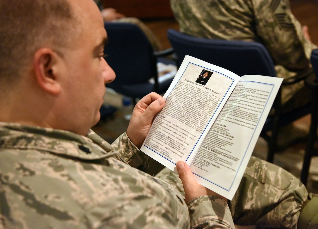 U.S. Air Force Lt. Col. Paul Fidler, 81st Mission Support Group deputy commander, reads an event program during the 81st Surgical Operations Squadron assumption of command ceremony at the Keesler Medical Center on Keesler Air Force Base, Mississippi, July 2, 2018.  The passing of the guidon is a ceremonial symbol of exchanging command from one commander to another. Lt. Col. Ryan Mihata, incoming 81st MSGS commander, assumed command during the ceremony. (U.S. Air Force photo by Kemberly Groue)
