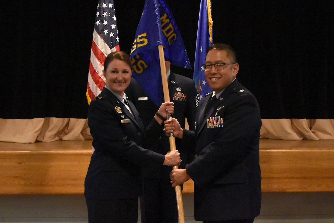 U.S. Air Force Col. Beatrice Dolihite, 81st Medical Group commander, passes the 81st Surgical Operations Squadron guidon to Lt. Col. Ryan Mihata, 81st MSGS commander, during the 81st MSGS assumption of command ceremony at the Keesler Medical Center on Keesler Air Force Base, Mississippi, July 2, 2018. The passing of the guidon is a ceremonial symbol of exchanging command from one commander to another. (U.S. Air Force photo by Kemberly Groue)