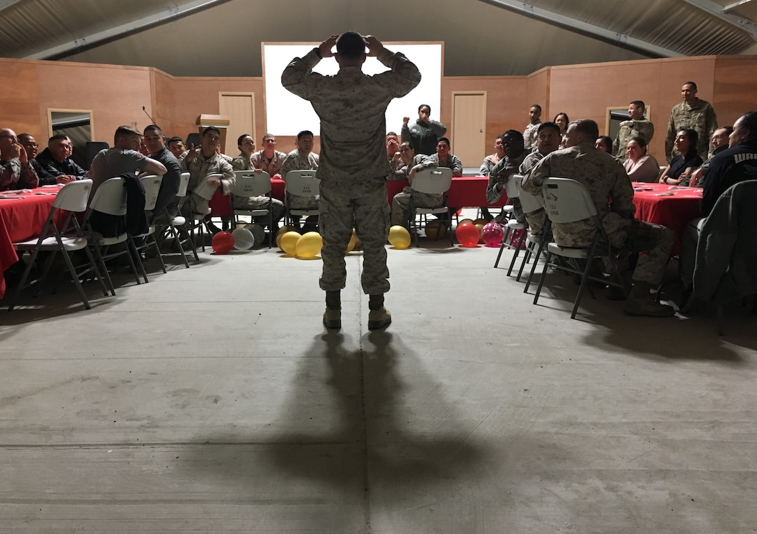 A U.S. Marine attempts to guess a mystery word, through clues given by his brothers and sisters-in-arms, during a monthly birthday celebration, 18 February 2017. Dinners such as these are often part of morale boosting events, while members serve in overseas locations.