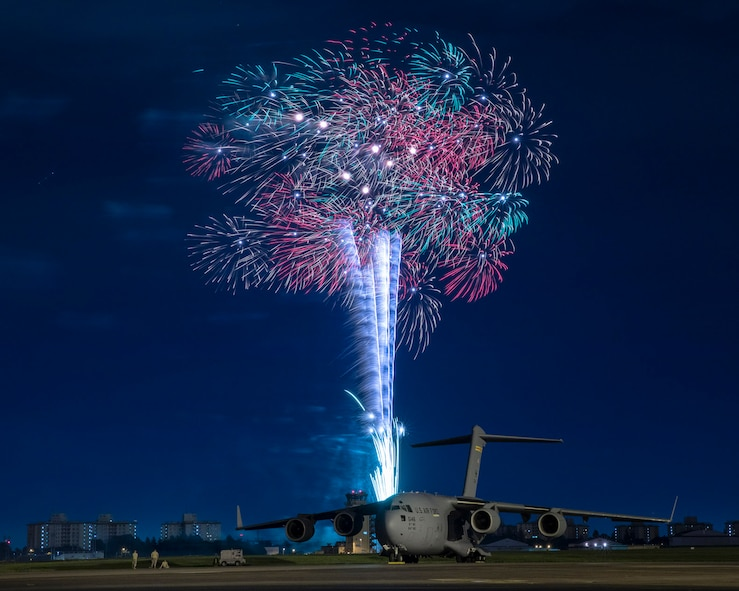 Fireworks explode behind a U.S. Air Force C-17 Globemaster III aircraft assigned to the 15th Wing during Celebrate America