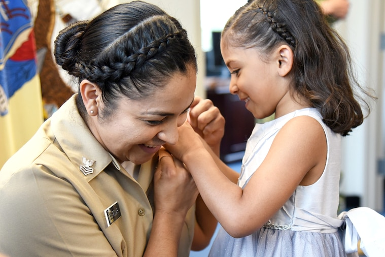 A child places a pin on her mother's uniform.