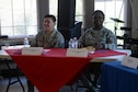 Two women wearing the Airmen Battle Uniform sit at a table with a red table cloth and smile at the camera.