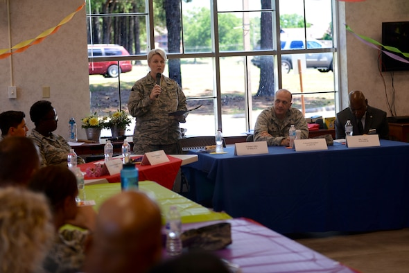 A woman wearing the Airman Battle Uniform speaks into a microphone into a circle of people also wearing the Airman Battle Uniform. They are sitting around tables with table cloths that are each a different color of the rainbow.