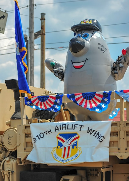 Winger, a caricature of a C-130H Hercules aircraft that serves as the 910th Airlift Wing's mascot, waves to the crowd during a Fourth of July parade in Austintown, Ohio.