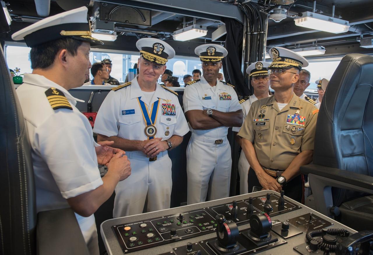 Naval officers talk on ship's bridge.