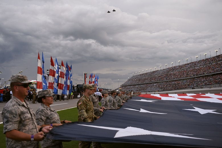 Service members display a 1,000 pound, football field-size American flag during the National Anthem as two F-22 Raptor aircraft conduct a fly over July 7, at the Daytona International Speedway in Daytona Beach, Fla. The F-22's were part of the 43rd Fighter Squadron at Tyndall Air Force Base, Fla. (U.S. Air Force photo by Airman 1st Class Zoe Thacker)