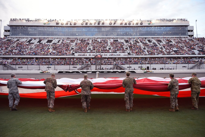 Service members gather a flag they unfurled July 7, at the Daytona International Speedway in Daytona Beach, Fla. The unfurling was part of the pre-race ceremonies for the Daytona Coke Zero Sugar 400 and NASCAR Salutes – NASCAR's recognition and honor of military members. (U.S. Air Force photo by Airman 1st Class Zoe Thacker)