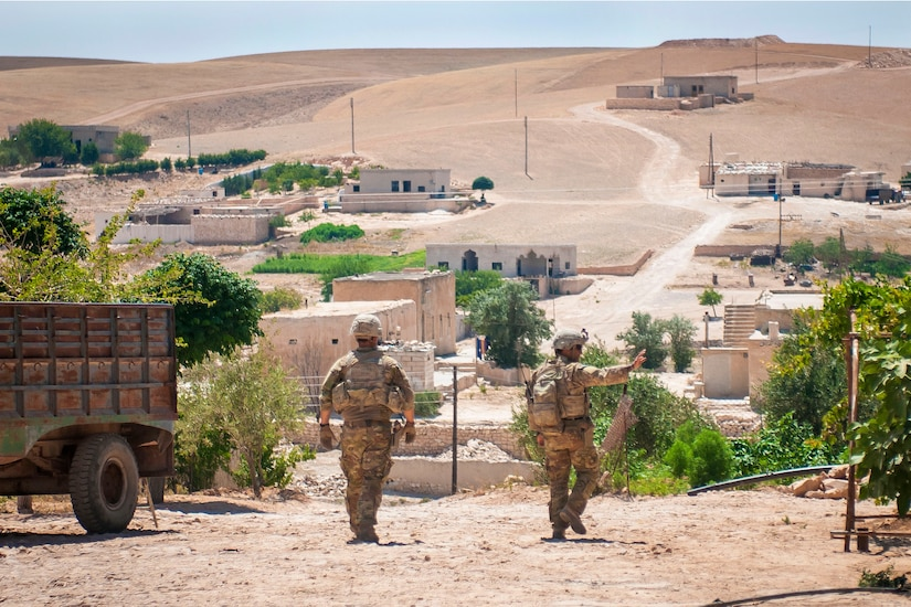 Soldiers wave to residents during a patrol.