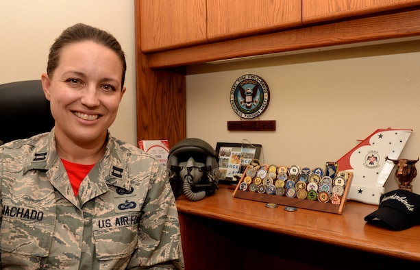Capt. Kristi Machado, 56th Force Support Squadron sustainment services flight commander, poses in front of memorabilia from her career June 29, 2018, at Luke Air Force Base, Ariz. Machado, a Florida native, first enlisted as a photographer in 2001. (U.S. Air Force photo by Senior Airman Ridge Shan)