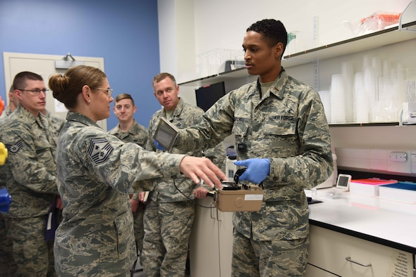 2nd Lt. Kaleb Mitchell, a chemist at the Air Force Radiochemistry Lab at Patrick AFB, Fla., checks Chief Master Sgt. Jessica Bender, command chief for the 9th Reconnaissance Wing, Beale AFB, Calif., for possible radioactive contamination using a hand-held radiation monitor.  Bender was one of 35 Airmen within 25th Air Force who visited DoD's sole nuclear treaty monitoring center June 1, 2018 to learn more about AFTAC's innovative mission.  (U.S. Air Force photo by Susan A. Romano)