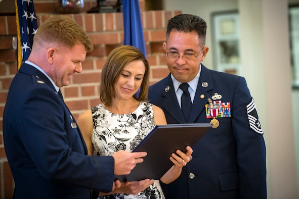 Lt. Col. Neal Van Houten, left, 23d Maintenance Squadron (MXS) commander, presents Jill Banghart with a certificate of appreciation during her husband Jay's retirement ceremony, July 6, 2018, at Moody Air Force Base, Ga. Banghart entered the Air Force in 1990 and served in numerous positions within the aircraft maintenance career field throughout his 28 year Air Force career. (U.S. Air Force photo by Airman 1st Class Eugene Oliver)
