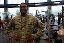 A man wearing the Airman Battle Uniform has his hands on his hips while looking at the camera with exercise equipment behind him. He's wearing glasses.