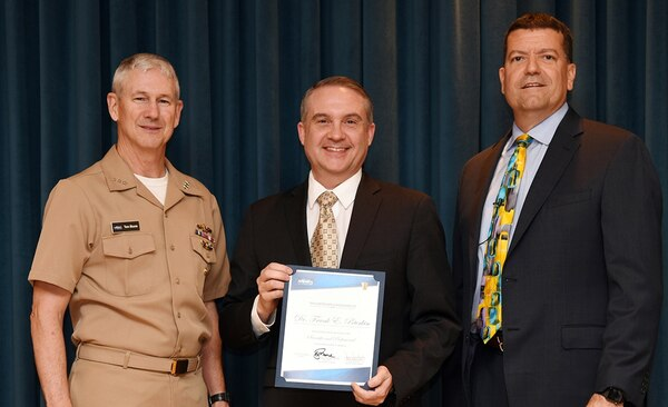 IMAGE: Vice Adm. Thomas Moore, commander of Naval Sea Systems Command (NAVSEA), and James Smerchansky, NAVSEA Executive Director, presented the Scientific and Professional Executive Award to NSWCDD engineer Dr. Frank Peterkin at a NAVSEA headquarters ceremony, June 18.   As the Navy's Distinguished Engineer for Directed Energy, Peterkin is responsible for assessing directed energy efforts across the Navy, technology development, and warfighting applications and for providing strategic direction in the development of directed energy capabilities. Peterkin is the driving technical force behind the Navy Laser Family of Systems which will result in the fielding of lasers onto surface ships.