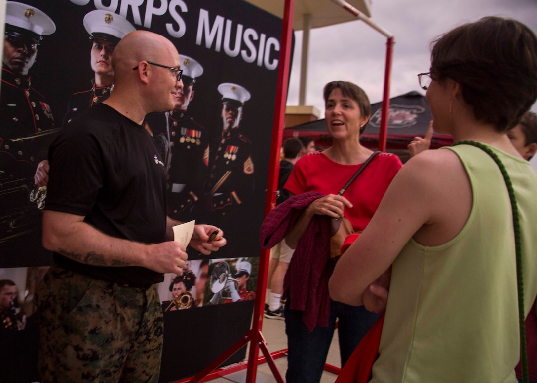 Gunnery Sergeant Matthew R. Phagan, the Music Technical Assistant with 6th Marine Corps District, speaks to attendees of the Drum Corps International at River Bluff High School in Lexington, South Carolina, July 07, 2018. The Drum Corps International creates a stage for the Marine Corps to engage in education, competition, and the promotion of individual growth. (U.S. Marine Corps photo by Lance Cpl. Jack A. E. Rigsby)